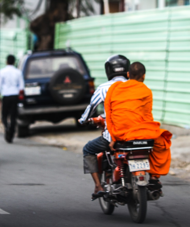 Monk riding on the back of  motorcycle.