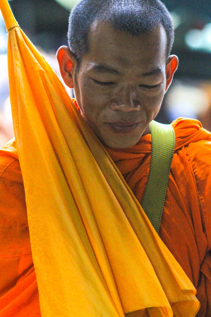 Monk giving a blessing after receiving alms.
