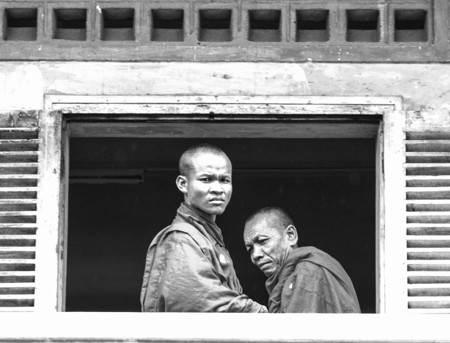 Two monks visiting the upstairs prison level. Most of the monks were killed during the Khmer Rouge regime.