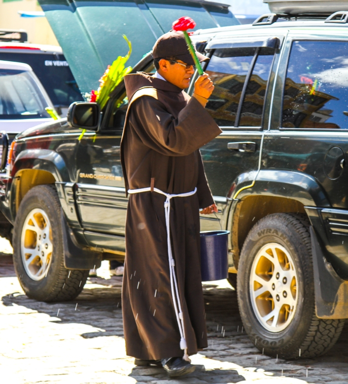 Priest blessing the car.