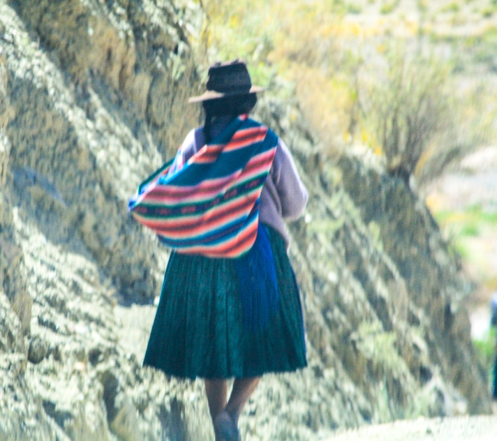 Indigenous woman walking along the mountain road.