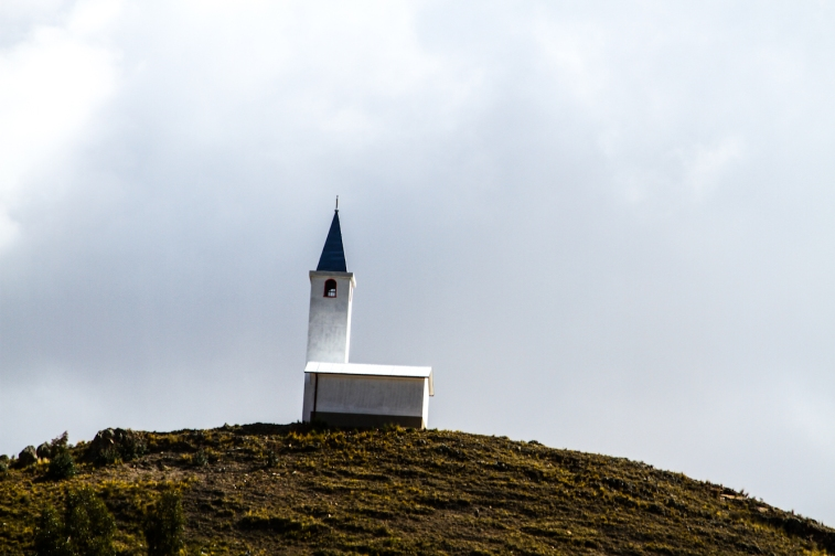 Tiny church seen on top of a hill.